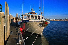 Lobster Boat At Christmas. This New England lobster boat was decorated for Christmas as its docked and waits for spring to begin its work for another season stock image