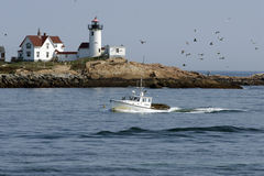 Lobster Boat Guided by Lighthouse Royalty Free Stock Photos