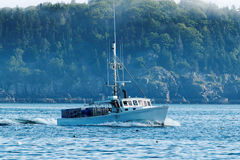 A lobster boat heads out to set his traps Stock Photos