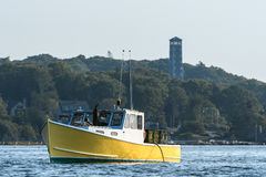 Lobster men hard at work on a beautiful morning in early autumn in South Bristol, Maine, United States. Lobster boat in South Bristol, Maine, New England, US royalty free stock photos