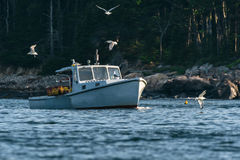 Lobster men hard at work on a beautiful morning in early autumn in South Bristol, Maine, United States. Lobster boat in South Bristol, Maine, New England, US Royalty Free Stock Photography