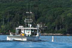 Lobster men hard at work on a beautiful morning in early autumn in South Bristol, Maine, United States. Lobster boat in South Bristol, Maine, New England, US stock photography