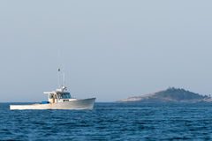 Lobster men hard at work on a beautiful morning in early autumn in South Bristol, Maine, United States. Lobster boat in South Bristol, Maine, New England, USn royalty free stock image