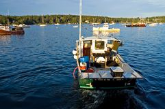Lobster boat at work. A  view of a lobster boat in the early morning light pulling away from the dock to head out into the open water for a day of work pulling Royalty Free Stock Photos