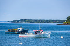 Lobster Boats at Anchor. Lobster boats lay at anchor in a small harbor in the Down East region of Maine Royalty Free Stock Image