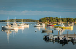 Lobster boats are moored in the harbor at dusk in Friendship, Maine. In beautiful calm, reflective blue water Stock Photo