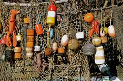 Lobster Buoys and Net. A fishing net is decorated with colorful wood buoys at a fishing village Stock Image