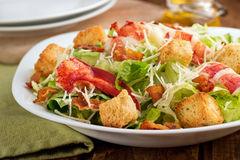 Lobster Caesar Salad. A crisp green lobster caesar salad with shredded parmesan cheese, crispy bacon, and herb croutons stock photos