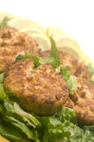 Lobster cakes  bed of lettuce with lemon slice wedges Royalty Free Stock Image