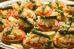 Lobster canapés. Appetizer toasts made of bread, tomato, lobster and asparagus under warm  light Royalty Free Stock Images