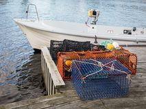 Lobster and crab traps standing on a pier next to a small boat. Traps for lobster and crabs standing on pier next to a white motor boat Stock Photo