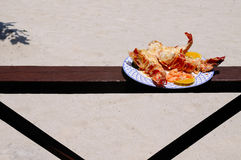 Lobster dinner. Plate of grilled lobster tales served on the beach Stock Photo