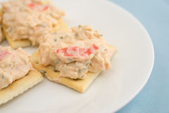 Lobster dip on saltine crackers on blue table cloth Stock Photo