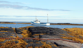 Lobster fishing boat Atlantic coast Nova Scotia. A picturesque landscape of fishing boat and rocky shore along the coast near Lunenburg,Nova Scotia Royalty Free Stock Image