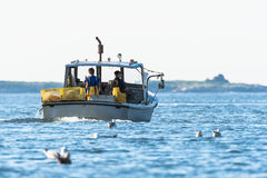 Lobster men hard at work on a beautiful morning in early autumn in South Bristol, Maine, United States Royalty Free Stock Images
