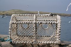 Lobster pot. Sitting on the edge of the quay waiting to go back on the boat to go out to sea stock photography