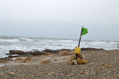 Lobster Pot Marker On The Beach - Flag In Stormy Windy Weather Royalty Free Stock Images