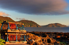 Lobster pot beside rocky shore Stock Photos