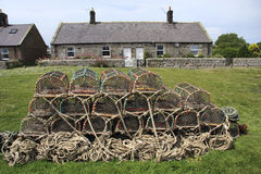 Lobster Pots and Cottages. A stack of Lobster Pots stored outside Cottages at Boulmer, a fishing village on the coast of Northeast England Royalty Free Stock Photos