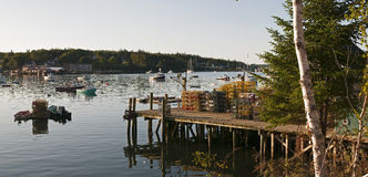 Lobster pots and fishing wharf. Lobster pots or traps on a waterfront wharf or pier with fishing boats in the background. Bass Harbor, Maine (USA Stock Photo
