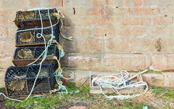 Lobster pots and stone wall at harbour stock images