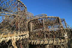 Lobster pots stacked up against blue sky. A stack of empty lobster pots ashore with a dark blue sky in the background royalty free stock photos