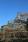 Lobster pots stacked up against blue sky. A stack of empty lobster pots ashore with a dark blue sky in the background, portrait aspect ratio stock image