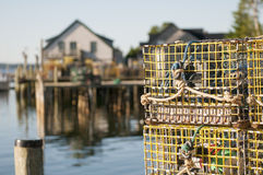 Lobster pots and wharf. Closeup of lobster pots or traps with a waterfront wharf or pier in the background. Bass Harbor, Maine (USA). Focus on pots Royalty Free Stock Image