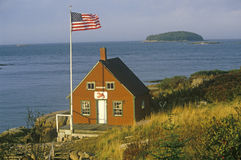 Lobster Shack in Maine. Red lobster shack overlooking the ocean with American flag flying in Maine Royalty Free Stock Image