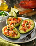 Lobster Stuffed Avocado. Delicious homemade lobster stuffed avocados with cucumber, tomato, jalapeno pepper, red onion and cilantro Stock Photos