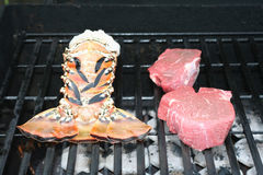 Lobster tail and steak. Still raw just starting to cook on grill Stock Images