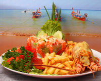 Lobster thermidor. Baked lobster served with shrimp cocktail and French fries Royalty Free Stock Photo
