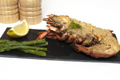Lobster Thermidor. Half a Lobster Thermidor with Asparagus Spears on slate plate royalty free stock photography