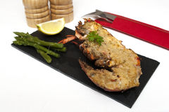 Lobster Thermidor. Half a Lobster Thermidor with Asparagus Spears on slate plate royalty free stock images