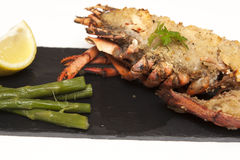 Lobster Thermidor. Half a Lobster Thermidor with Asparagus Spears on slate plate stock images
