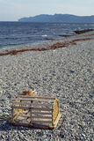 Lobster trap and pebble beach in Canada Royalty Free Stock Image