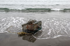 Lobster trap on the shore. Single old lobster trap resting on the shore of beach Royalty Free Stock Photography
