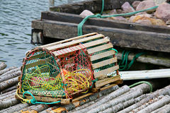 Lobster Trap. A wooden lobster trap with buoys and rope on a wharf in Newfoundland, Canada Stock Photo