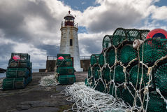 Lobster traps and lighthouse in Lybster, Scotland. Stock Images