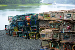 Lobster Traps piled on Shore line. Old and new design lobster traps stacked on a shore line after lobster season. Cape Breton, Nova Scotia Royalty Free Stock Images