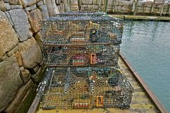 Lobster Traps Stacked on Dock. Lobster traps are stacked on a dock against the sea wall of a harbor Stock Photo