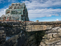 Lobster Traps on Stone Pier, Orkney. A pyramidal pile of lobster traps, or creels, are stacked up on the old stone pier, Papa Westray, Orkney Stock Images
