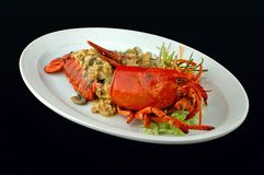 Lobster with vegetables on a dish. The lobster on a dish on a black background Royalty Free Stock Photos