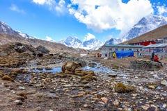 Lobuche,尼泊尔04/16/2018 :小村庄和牦牛与美丽的雪加盖了山作为背景 图库摄影