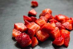 Lobule sliced strawberries. On black slate background Royalty Free Stock Photo