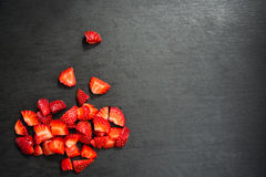 Lobule sliced strawberries. On black slate background Stock Photos