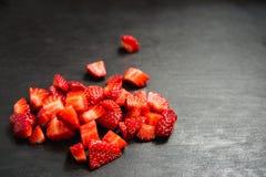 Lobule sliced strawberries. On black slate background Stock Images