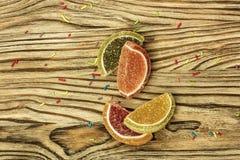 Lobules av färgrik marmelad ligger på en träyttersida Royaltyfri Bild