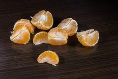 Lobules av mandarinen på den mörka trätabellen Fotografering för Bildbyråer
