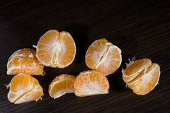 Lobules of mandarin on dark wooden table. Lobules of mandarin on the dark wooden table royalty free stock images